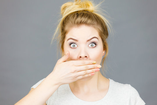 Woman covering her mouth with hand