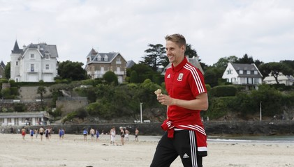 Wales' national soccer player Edwards eats an icecream as he walks on the beach in Dinard