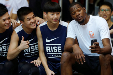 NBA player Durant takes a selfie with local school basketball players during a promotional event in Hong Kong