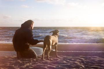 Mann und Weimaraner Jagdhund genießen die Zeit am Meer