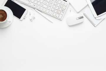 overhead of white office table with notebook, computer keyboard and mouse, tablet pc and smartphone. copy space