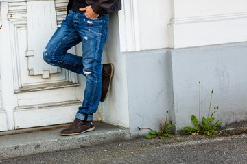 Man in blue jeans in front of old doorstep