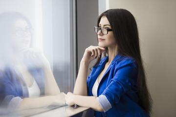 Pondering businesswoman in glasses in lobby
