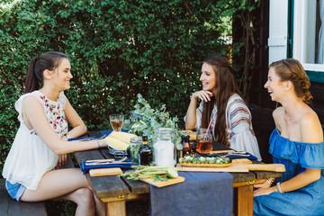 Drei Frauen draußen am Tisch mit Essen
