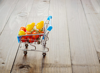Closeup red shiny cherry tomatoes in the blue shopping cart on dark wooden background