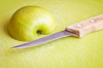 Green apple cut in slices on a cutting board with a steel knife with wooden handle illustrative. Apple has a content of numerous minerals and vitamins. It is one of the world's healthiest foods.