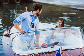 Handsome captain with girl in boat on lake