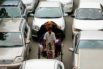 Women wearing burqa ride on a rickshaw in Dhaka