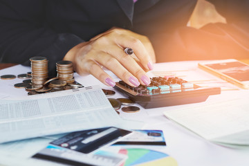 business woman hand analyzing financial data, account book,business graph with pile of coins ,stock chart and credit card background  Wall mural