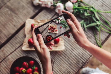 Girl's hands taking photo of breakfast with strawberries by smartphone. Healthy breakfast, Clean eating, vegan food concept. Top view