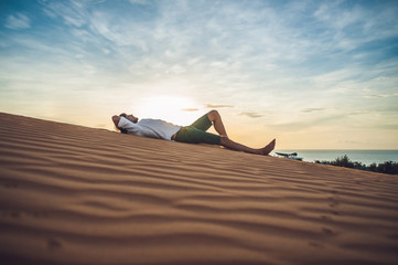 Spoed Foto op Canvas Ontspanning A man sits on the sand in the desert