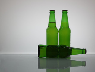 The light shines from the back of a bottle of green beer,and it has a shadow on the floor.
