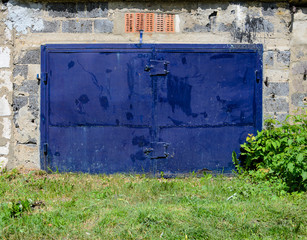 Garage facade with old dark blu gates. Old garage door
