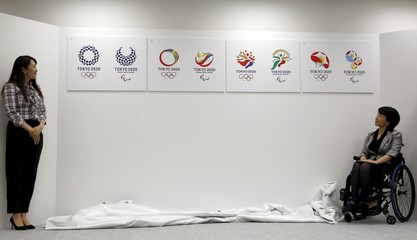 Members of the Tokyo 2020 Emblems Selection Committee, former tennis player Sugiyama and Taguchi, look at four shortlisted emblem designs for the Tokyo 2020 Olympic and Paralympic Games after unveiling them in Tokyo, Japan
