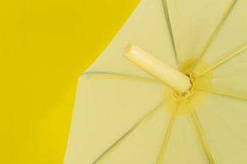 A yellow umbrella on yellow background