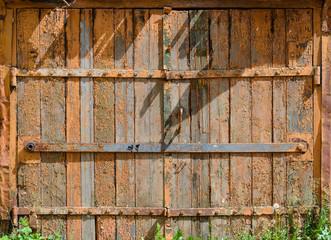 Old painted wooden garage door of brown color
