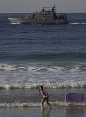 A Brazilian Navy ship patrols along Copacabana Beach in Rio de Janeiro