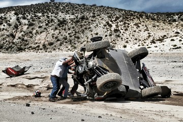Loeb of France is helped to push his car back after he had an accident which turned the car over during the eighth stage in the Dakar Rally 2016 near Cafayate