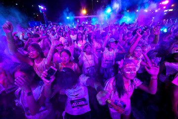 Multi-coloured dyes are thrown in the air by participants during the Blacklight Run Thailand in Bangkok