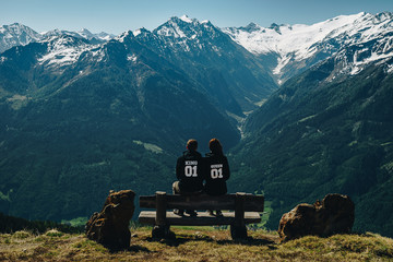 Junges Paar auf einer Bank in den Alpen