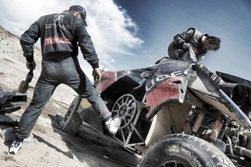Loeb of France and co-pilot Elena work on his car after he had an accident during the eighth stage of the Dakar Rally 2016 near Belen