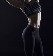 Portrait of beautiful bodybuilder woman's belly over black background. Healthcare and fitness concept.