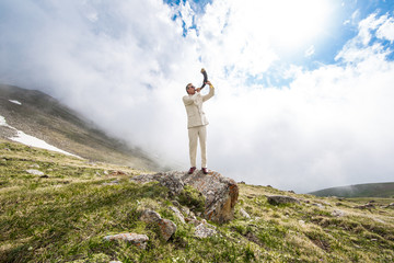 Businessman in a white suit blowing in the horn in the mountains