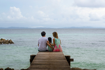 Happy family sitting on wooden walkway looking sea and sky
