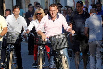 French President Emmanuel Macron and his wife Brigitte ride their bicycles as they leave their home in Le Touquet