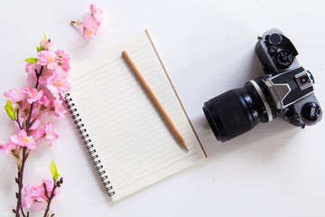 Sakura,camera and Notebook on wooden table,Top view