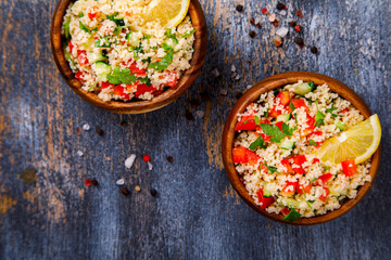 Tabbouleh salad with couscous on the plate.Traditional middle eastern or arab dish.Vegetarian.Parsley,pepper,cucumber,tomato,lemon.Middle eastern meze.Food or Healthy diet concept.Copy space for Text.