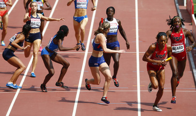 US and Britain pass the baton during their women's 4 x 400 metres relay heat at the 15th IAAF Championships in Beijing