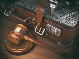 Gavel and suitacse full of money. Concept for corruption, business crime or paying an auction.