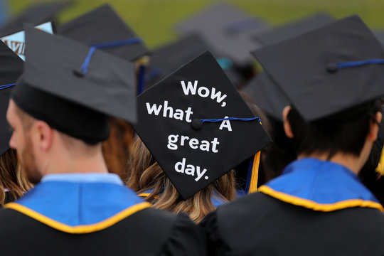 Messages and artwork are pictured on the top of the caps of graduating students during their graduation ceremony at UC San Diego in San Diego