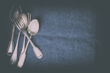 Old Vintage  Silverware Spoons on a dark textile background.Antique.Top View.Copy space for Text.Toned image.Vintage style.selective focus.