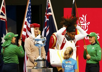 Williams of the U.S. adjusts her hair while walking past the women's singles trophy as she arrives for her final match against Germany's Kerber at the Australian Open tennis tournament at Melbourne Park