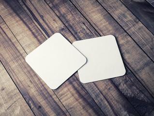 Two blank square beer coasters on wood table background.