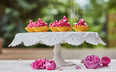 Pink cupcakes decorated with pearls, hearts and roses on the terrace