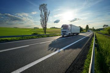 Fotobehang - White trucks driving on asphalt road along the green fields in rural landscape at sunset