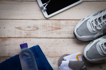 Sport shoes,sock, mobile phone , towel and water on wood background