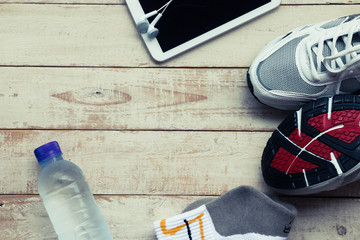 Sport shoes, mobile phone , sock and water on wood background