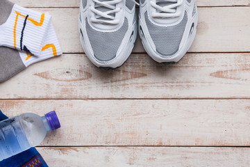 Sport shoes, sock , towel and water on wood background