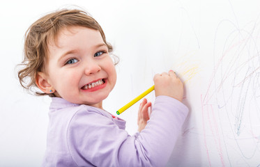 Adorable child drawing on the wall