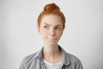 Indoor portrait of young woman of extraordinary appearance looking aside with pensive look raising her ginger eyebrows and pressing lips planning her meeting trying to decide something important