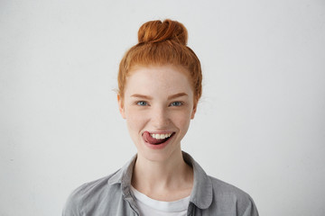 Young teenage female with ginger hair knot sticking out her tongue having funny look isolated over white background. Freckled student girl having fun being happy to finish her studying successfully