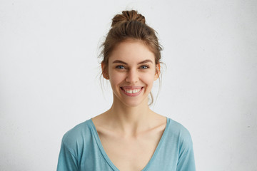 Headshot of pleasant-looking young Caucasian woman with broad smile showing her straight white teeth being happy with positive news. Woman with pleasant smile posing against white background