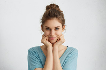 Horizontal portrait of cute young woman with blue eyes and gentle smile holding hands under chin looking contented and carefree. Pretty cheerful female student posing against white background