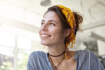 Style, fashion and clothing concept. Trendy woman having yellow scarf on head and wearing stripped shirt having carefree expression looking up. Positive hipster woman isolated over white walls Fotoväggar