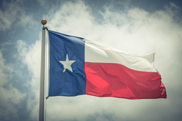 Large Texas (The Lone Star) flag waving on flag pole with cloud blue sky. Windy and sunny day with waving flag blowing/flowing. Ruffled Texas flag. Room for text, copy space. Vintage tone.