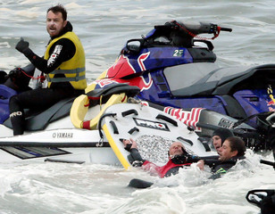 Rescue swimmers brace the neck of Allport with their hands after he wiped out during competition at the Cape Fear surfing tournament off Sydney's Cape Solander in Australia